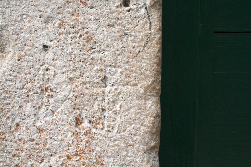 1. Antropomorfni križ u kružnici (križ u obličju čovjeka) i motiv srca na dovratniku Kalalarge 1 u Makarskoj (fotografija: Marinko Tomasović)
